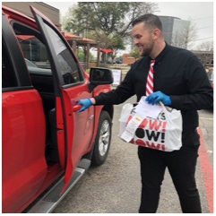 TGI Fridays employee delivering takeout bags to a customer's vehicle for curbside pickup