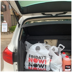 TGI Fridays takeout bags sitting in the open trunk of a vehicle